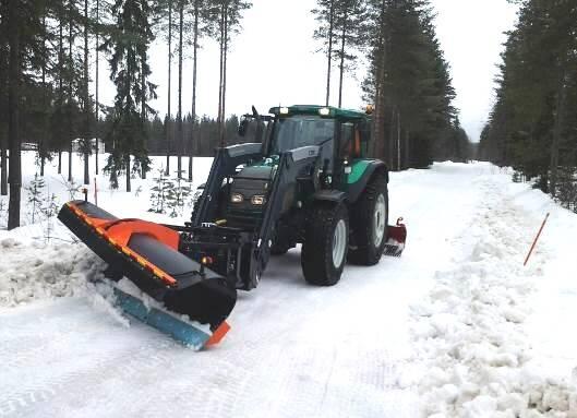 Lumiauralla varustettu traktori auraamassa lumista metsätietä.