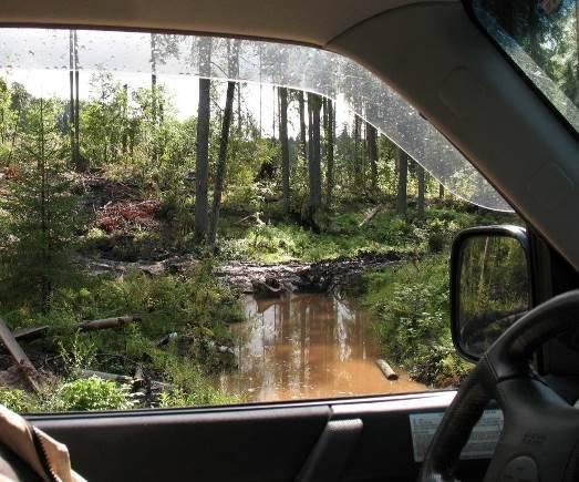 Kuvassa ajoura on tukkinut metsätien laskuojan. Tie pehmenee nopeasti, ellei tukosta avata