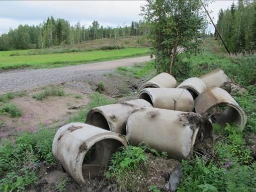 Käytettyjä betonirummun renkaita tien vieressä.