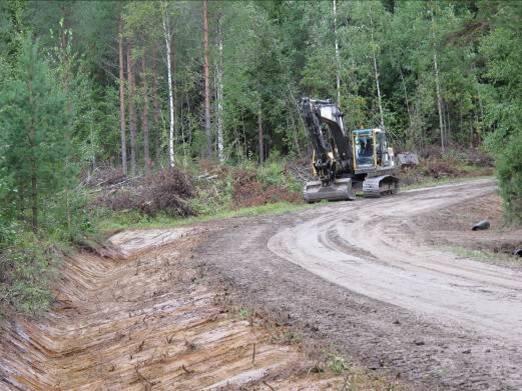 Kaivinkone perkaa metsätien sivuojia.