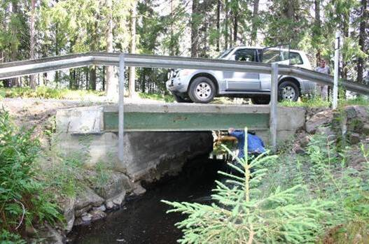 Kuva puron ylittävästä sillasta, jonka päällä on maastoauto.